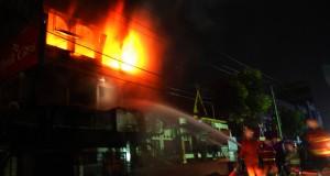 Petugas pemadam kebakaran berusaha memadamkan api yang membakar ruko gudang penyimpanan petasan di Pekanbaru, Riau