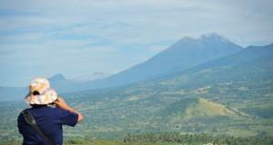 Seorang wisatawan mengambil foto panorama gunung Rinjani dari pelabuhan Kayangan, Selong,