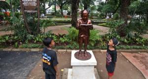 Dua anak melihat patung masa kecil KH. Abdurahman Wahid di Taman Amir Hamzah, Jakarta, Minggu (26/4).