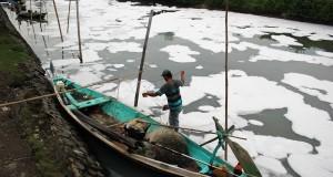 Nelayan menata jaring saat muara sungai Tambak Wedi dipenuhi dengan limbah berbentuk busa puith di Surabaya, Jawa Timur, Minggu (26/4).