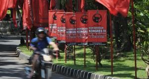 Seorang wisatawan mengendarai kendaraan di samping bendera dan poster PDI-P menjelang Kongres IV PDI-P di Sanur, Bali, Senin (6/4).