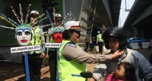 Seorang anggota Polwan membantu seorang pengendara motor, memasangkan helm di kepalanya saat gelar operasi Simpatik Jaya 2015 di kawasan Jalan Gatot Subroto, Jakarta, Rabu (1/4).