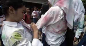 Beberapa siswa SMP saling membubuhkan tanda tangan di seragam usai pelaksanaan hari terakhir Ujian Nasional (UN), Makassar, Sulawesi Selatan, Kamis (7/5). Meski pihak sekolah di kota Makassar telah menghimbau para siswanya untuk menggelar kegiatan positif usai Ujian Nasional namun sejumlah siswa tetap meluapkan kegembiraan dengan  melakukan aksi coret-coret ataupun konvoi di jalan raya. ANTARA FOTO/Dewi Fajriani/Rei/pd/15.
