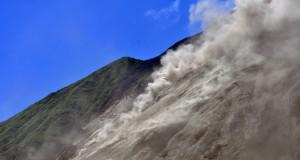 Gunung api Karangetang mengeluarkan awan panas di Kabupaten Kepulauan Sitaro, Sulawesi Utara, Jumat (8/5). sejak erupsi terus menerus mulai dari tiga pekan lalu kampung Kora-Kora Kelurahan Bebali Kecamatan Siau Timur hancur dan sekitar  400 penduduk mengungsi ke tempat lebih aman. ANTARA FOTO/Fiqman Sunandar/Asf/nz/15.