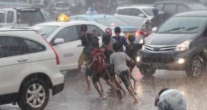 Sejumlah anak bermain hujan di kawasan Jalan Balikpapan, Jakarta, Senin (4/5). Menurut data BMKG, saat ini telah berlangsung masa peralihan musim atau pancaroba dari musim hujan ke musim panas dimana kondisi tersebut memicu cuaca yang tak menentu, seperti cuaca panas di pagi hari dan hujan deras disertai angin kencang di sore hari. ANTARA FOTO/Muhammad Adimaja/ed/Spt/15