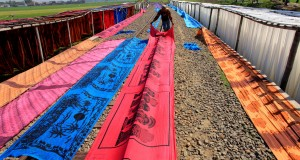Pekerja menjemur kain rayon untuk sarung pantai di sekitar jalur rel kereta api di Mojolaban, Sukoharjo, Jawa Tengah, Kain yang telah kering selanjutnya dibentuk sarung pantai untuk didistribusikan ke berbagai kawasan wisata pantai di Jawa dan Bali. ANTARA FOTO/Maulana Surya/Rei/15.