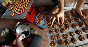 Ibu rumah tangga mengerjakan pesanan kue kering di rumahnya, Medan, Sumatera Utara, Sabtu (27/6). Sejumlah ibu rumah tangga memanfaatkan waktu luangnya untuk berbisnis kue kering skala rumahan menjelang Lebaran. ANTARA FOTO/Septianda Perdana/ed/foc/15.