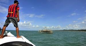 Nelayan memperhatikan bagang ikan miliknya di Pantai Sinjai, Kabupaten Sinjai, Sulawesi Selatan, Sabtu (18/7). Bagang yang terbuat dari bambu tersebut digunakan untuk menangkap ikan-ikan kecil yang kemudian diolah menjadi ikan kering. ANTARA FOTO/Yusran Uccang/Rei/Spt/15.