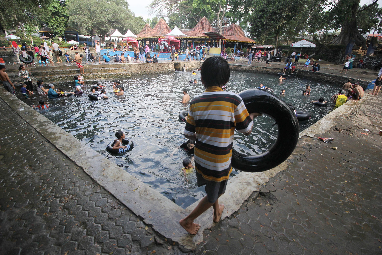 Warga memadati pemandian Banyu Biru di Pasuruan, Jawa Timur, Senin (20/7). Sejumlah warga memanfaatkan libur Lebaran untuk mengunjungi tempat wisata bersama keluarga. ANTARA FOTO/Moch Asim/zk/asf/15.