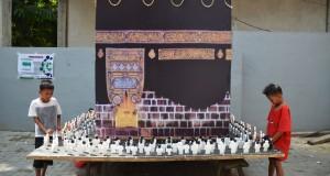 Dua orang anak memperhatikan miniatur Ka'bah yang dibuat warga di Lingkungan Peresak Tempit, Ampenan Tengah, Mataram, NTB, Kamis (16/7). Guna memeriahkan malam takbiran Idul Fitri 1 Syawal 1436 H nanti sejumlah warga di kota Mataram mulai mempersiapkan berbagai macam hiasan seperti replika masjid, miniatur ka'bah, dan lampion untuk diarak keliling kota bersama warga lainnya. ANTARA FOTO/Ahmad Subaidi/Rei/ama/15.