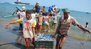 Sejumlah nelayan menurunkan keranjang berisi ikan hasil tangkapannya di Pantai Ampenan, Mataram, NTB, Selasa (21/7). Memasuki H+ 4 Lebaran para nelayan di kawasan Pantai Ampenan mulai kembali beraktivitas. ANTARA FOTO/Ahmad Subaidi/Rei/kye/15.