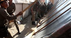 Satuan Polisi Pamong Praja (Satpol PP) dibantu aparat kepolisian dan TNI melakukan penertiban pembongkaran paksa lapak pedagang di sepanjang pusat Perdagangan dan Sukaramai Pusat kota Lhokseumawe, Provinsi Aceh. Senin (27/7). Penertiban pembongkaran paksa lapak itu terpaksa dilakukan karena pedagang membandel tidak mengindahkan intruksi pemerintah kota untuk pindah ke tempat baru hingga batas waktu yang diberikan 27 Juli 2015. ANTARA FOTO/Rahmad/ed/foc/15.
