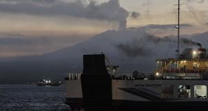 Sebuah kapal ferry yang membawa pemudik menunggu bersandar dengan latar belakang erupsi Gunung Raung pada H-5 Lebaran di Pelabuhan Gilimanuk, Jembrana, Bali, Minggu (12/7). Arus mudik dari Bali ke Jawa dan Sumatera lewat jalur darat melalui pelabuhan tersebut diprediksi mengalami peningkatan menyusul penutupan Bandara Ngurah Rai berulang kali akibat erupsi Gunung Raung. ANTARA FOTO/Nyoman Budhiana/ss/foc/15.