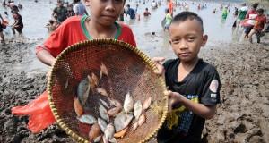 Dua anak menunjukkan ikan yang berhasil di dapat saat mengikuti tradisi Ngubek Setu di Setu Jatijajar, Tapos, Depok, Jawa Barat, Minggu (26/7). Tradisi Ngubek Setu merupakan kegiatan tahunan memanen ikan sekaligus sebagai ajang silaturahmi. Tradisi tersebut dilakukan warga saat debit air danau menyusut di musim kemarau. ANTARA FOTO/Indrianto Eko Suwarso/asf/kye/15.