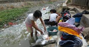 Warga saat mencuci di saluran kali irigasi yang mulai surut akibat kemarau, Teluknaga, Kabupaten Tangerang, Banten, Jumat (31/7). Warga terpaksa mencuci di kali untuk menghemat persedian air bersih dirumahnya yang mulai menyusut akibat kemarau. ANTARA FOTO/Lucky R./ss/pd/15