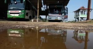 Pengemudi membersihkan busnya yang terparkir di Terminal Pondok Cabe Udik, Tangerang Selatan, Senin (3/8). Terminal yang akan digunakan untuk menggantikan Terminal Lebak Bulus tersebut akan kembali dilanjutkan pembangunannya dengan bantuan biaya (hibah) dari Pemprov DKI Jakarta sekitar Rp64,8 milliar dan dimulai pembangunannya pada awal tahun 2016. ANTARA FOTO/Muhammad Adimaja/Rei/15.