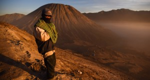 Warga berjalan di bibir kawah Gunung Bromo dengan latar Gunung Bathok, Probolinggo, Jawa Timur, Sabtu (1/8). Wisata gunung tersebut ramai dikunjungi wisatawan baik dari dalam negeri ataupun luar negeri karena bertepatan dengan perayaan Yadnya Kasada. ANTARA FOTO/Zabur Karuru/ed/pd.15